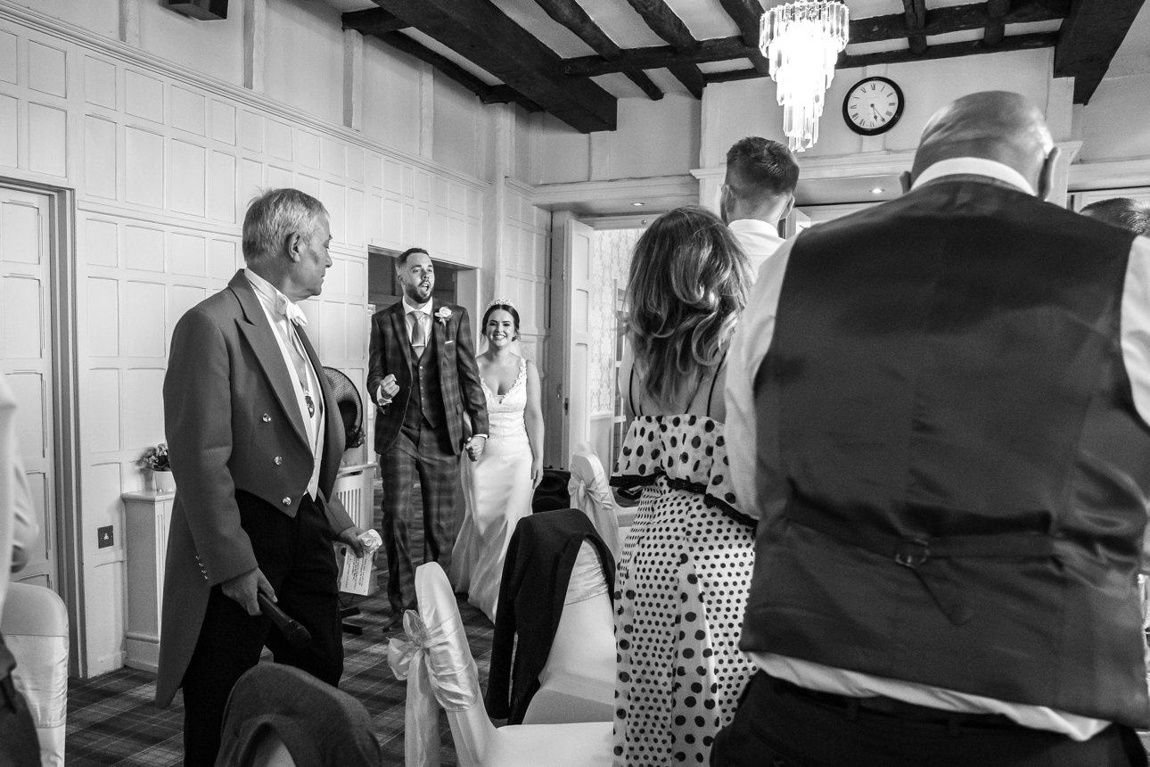 The bride and groom enter The Manor Elstree wedding breakfast while guests stand and wait for them.