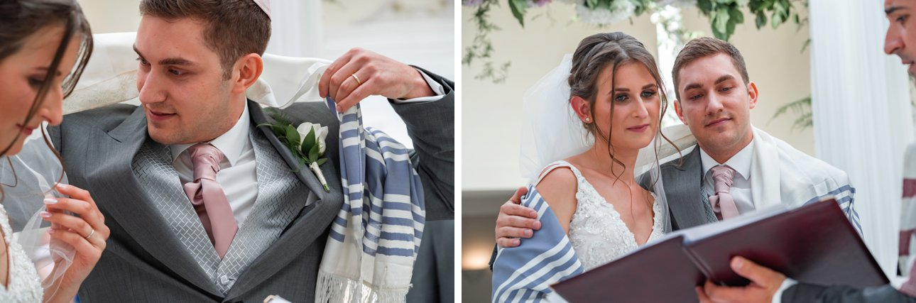 The groom wraps his tallit or prayer shawl around his new wife during their Jewish marriage ceremony at Stapleford Park.