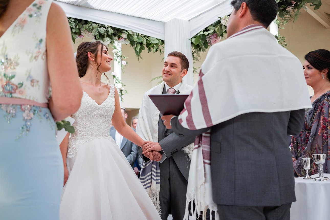 The bride and groom look at each other under the chuppah during their Jewish marriage ceremony at Stapleford Park in Leicestershire.