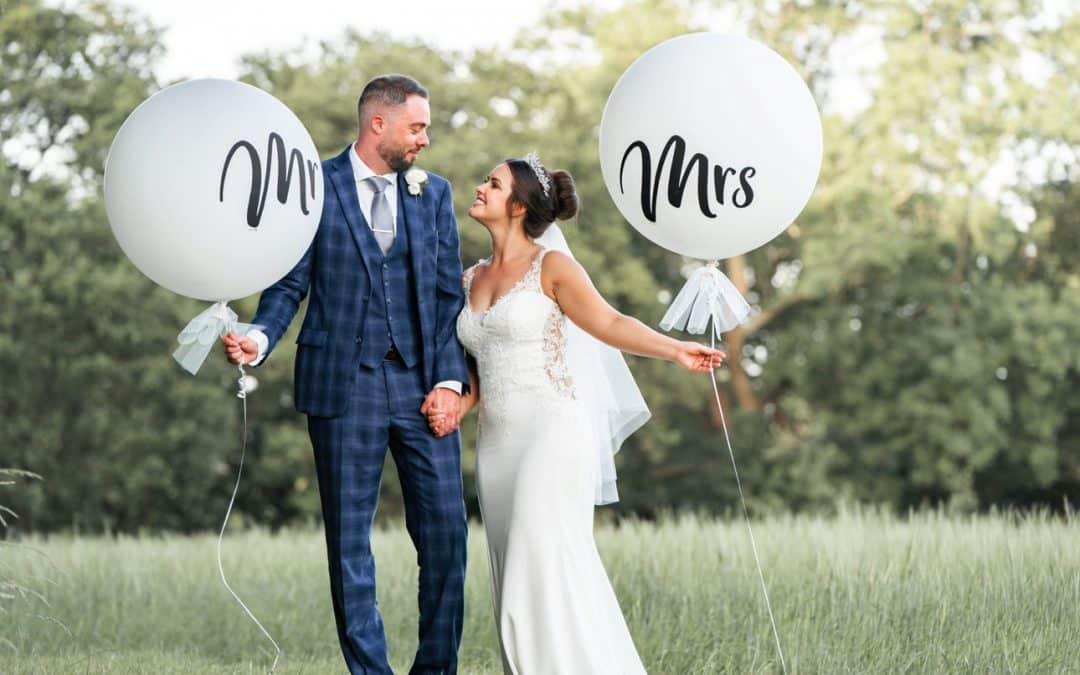 couple-holding-balloons-walking-in-green-fields