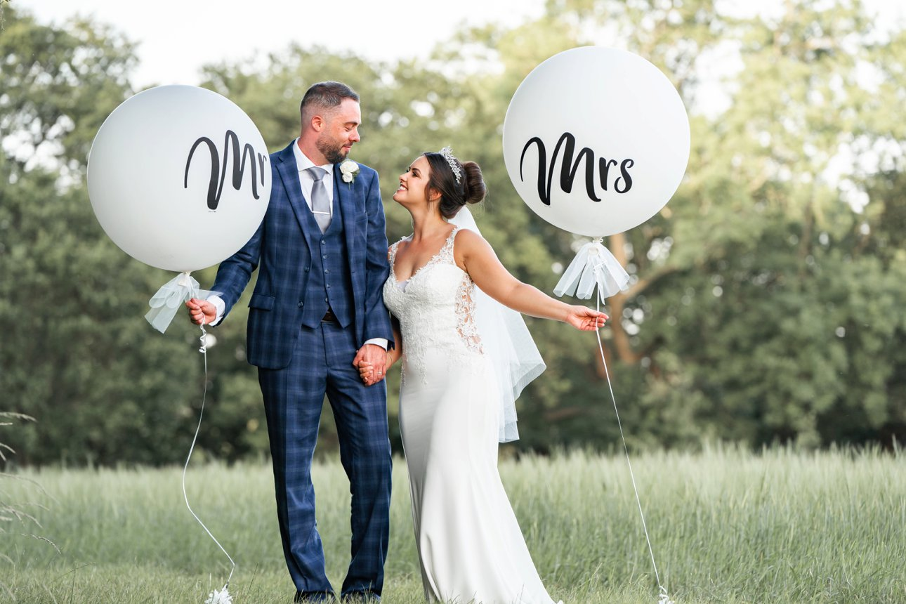 The bride and groom hold large circular balloons with Mr and Mrs on them.