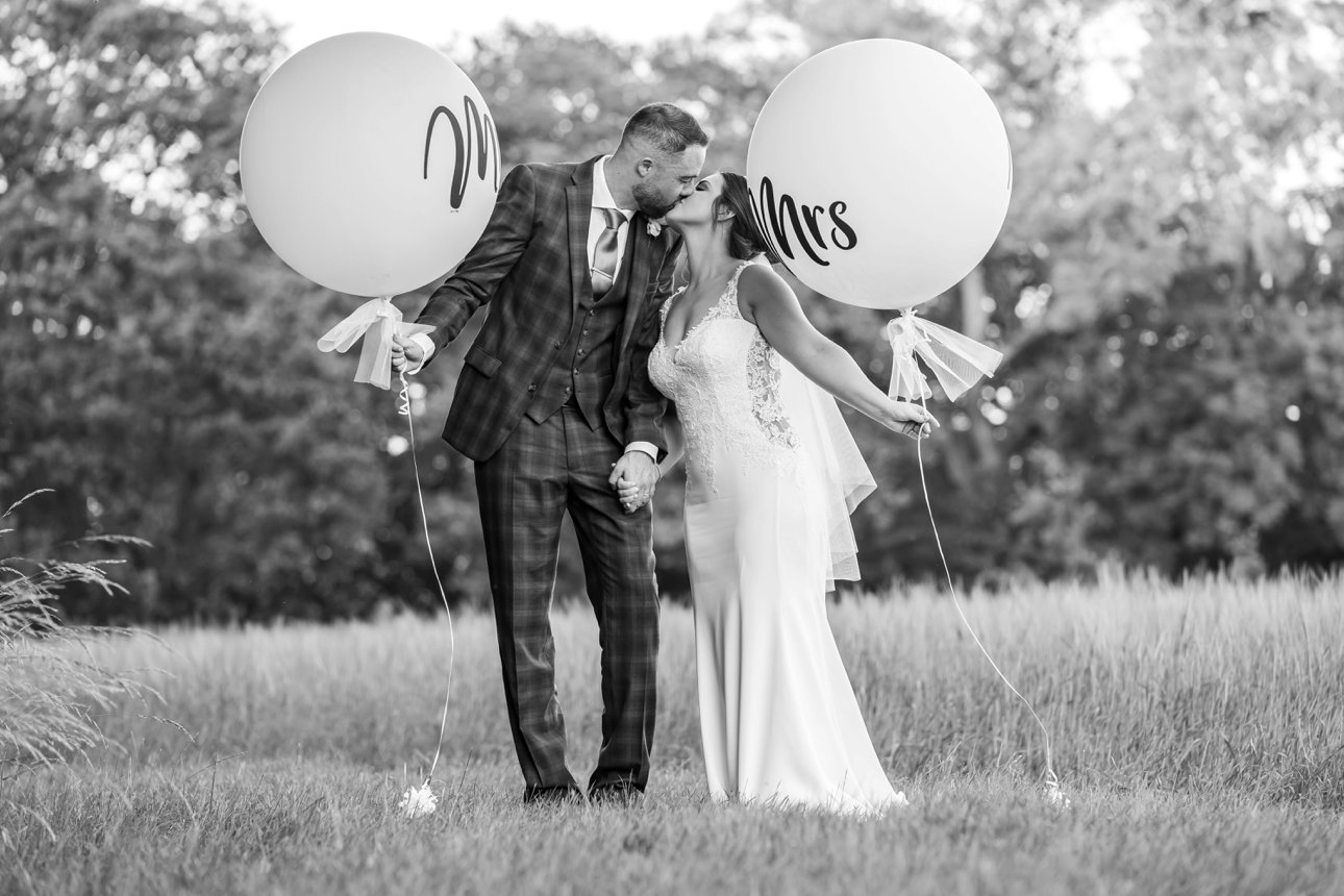The bride and groom kiss while holding large circular balloons with Mr and Mrs on them.