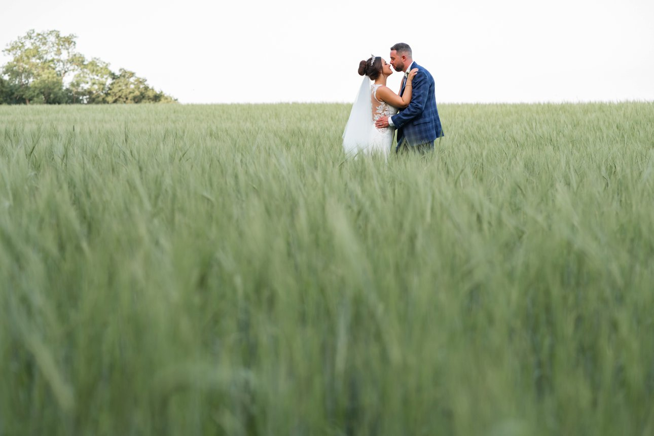 The bride and groom standing in a green field of wheat for their portraits.