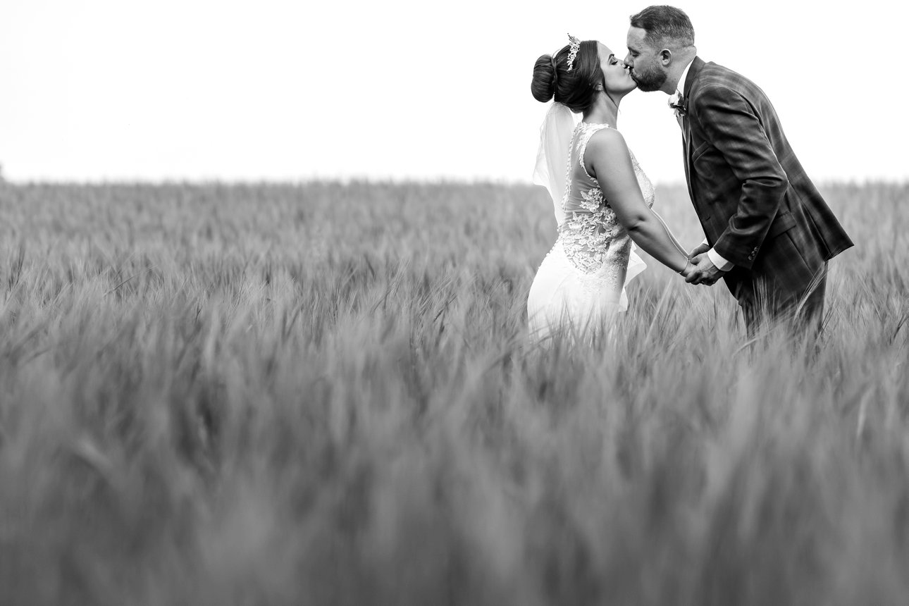 The bride and groom kiss in a field of wheat. It's a black and white photo.