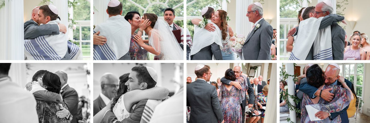 The bride, groom and families hug after their Jewish wedding ceremony.