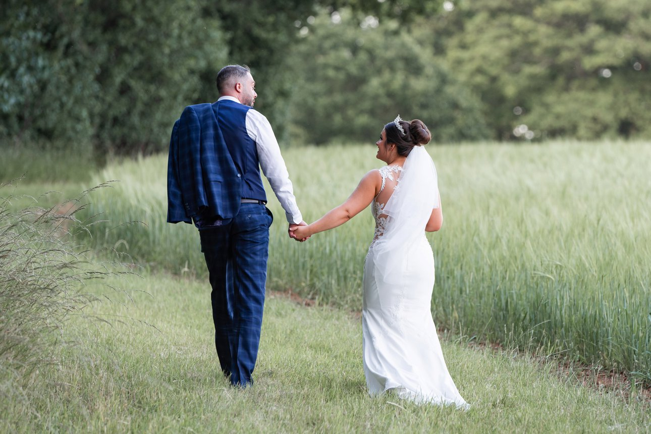 The bride and groom walk away in a wheat field.