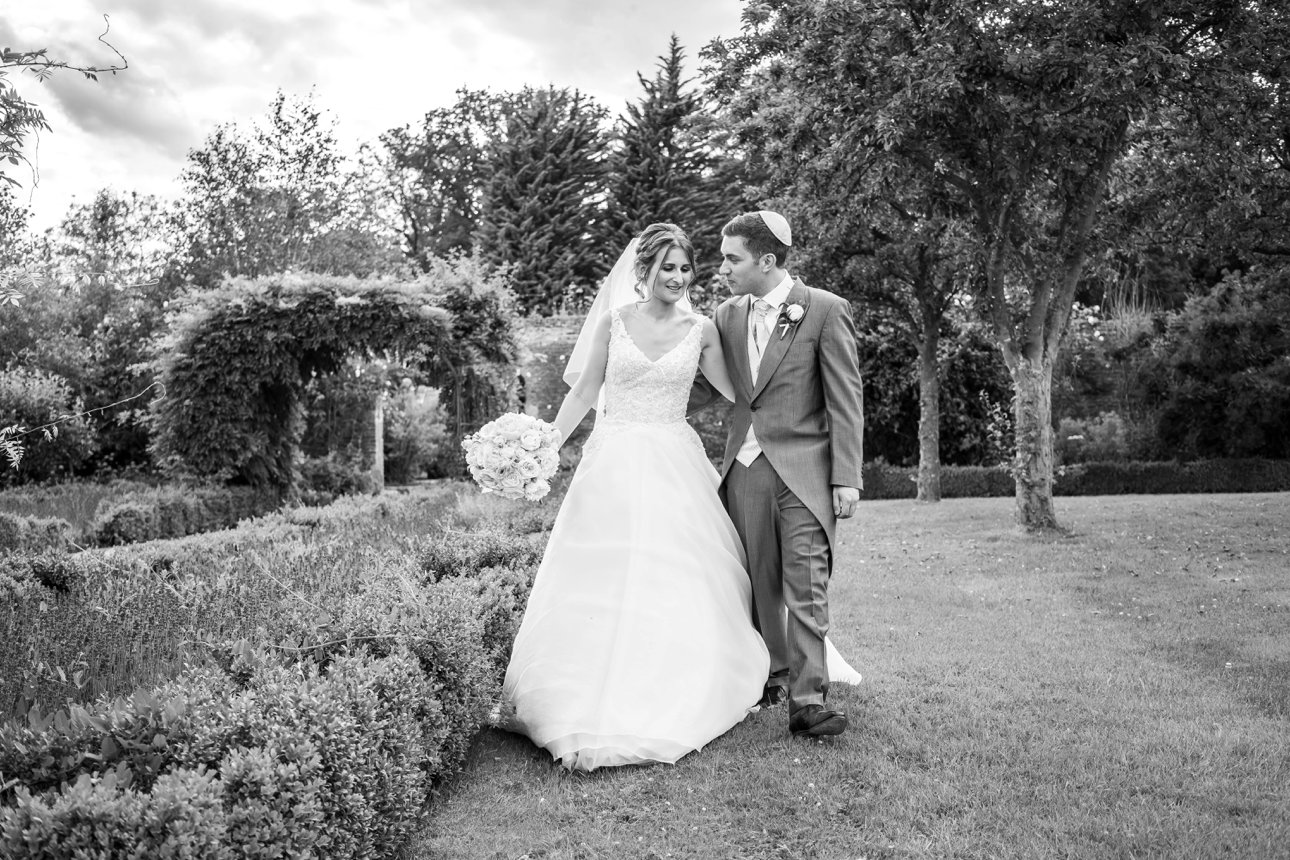 A bride and groom walk through the grounds of Stapleford Park.