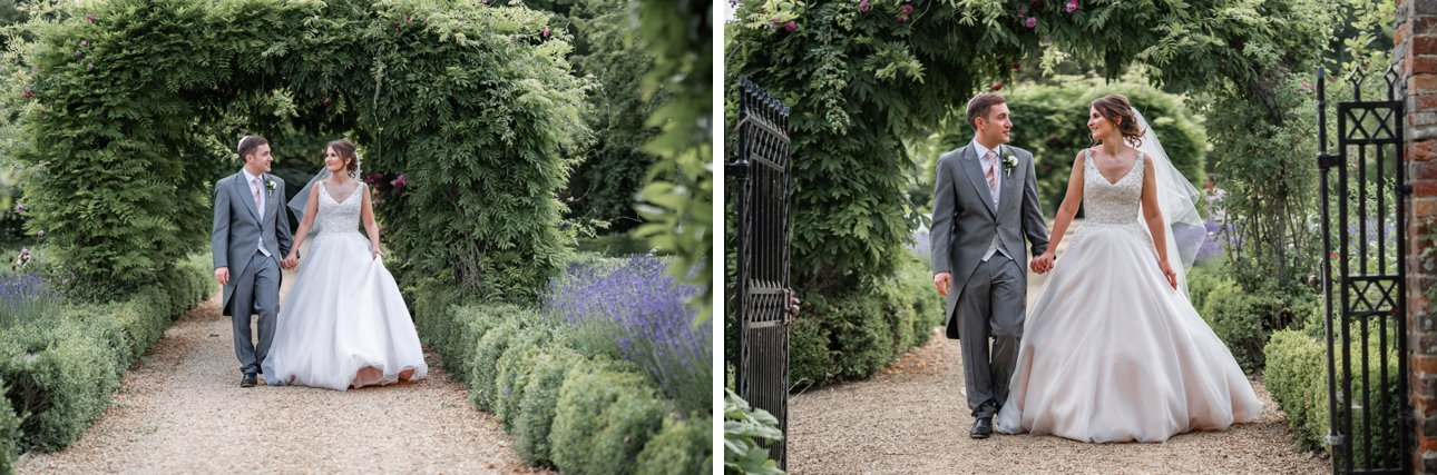 A bride and groom walk through the lush grounds of Stapleford Park.