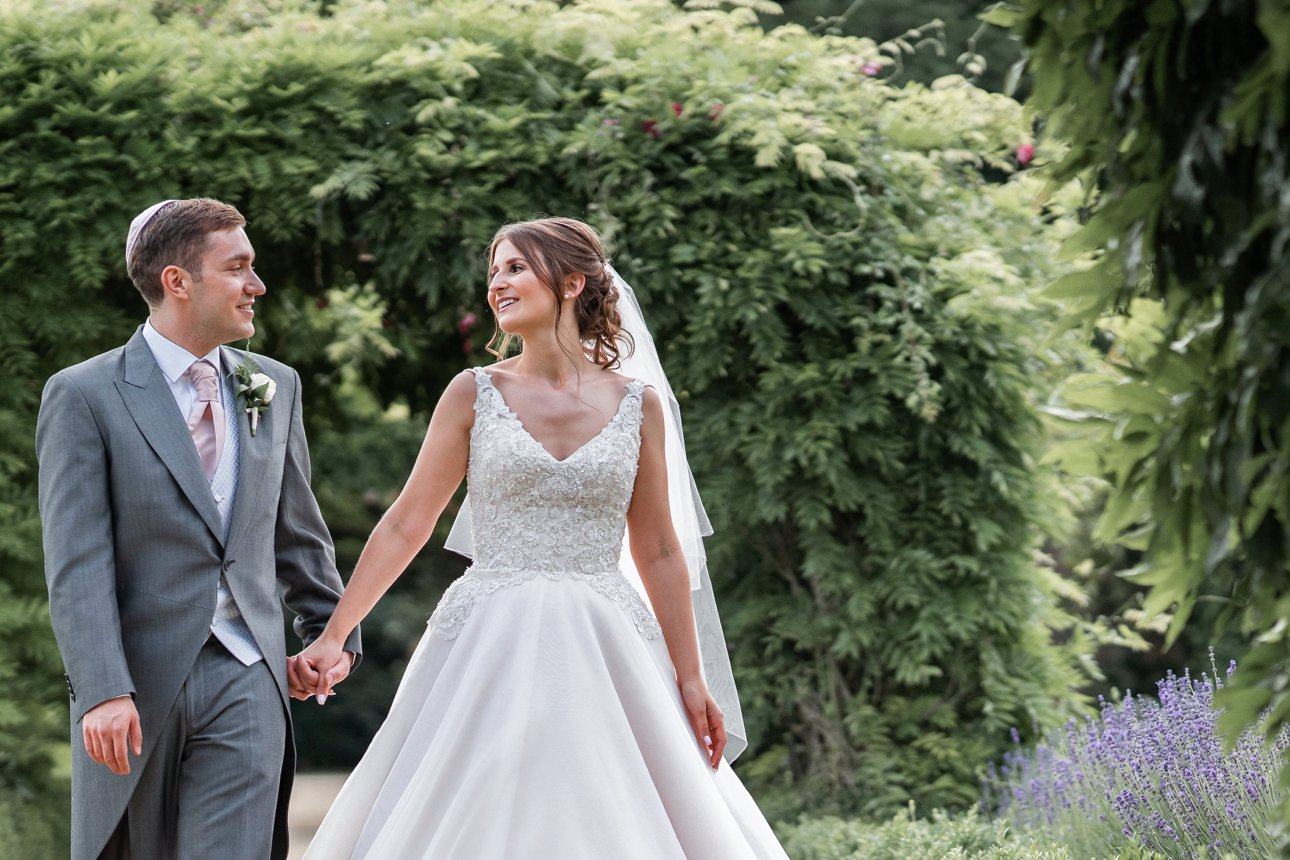 A bride and groom walk hand in hand through the lush greenery of Stapleford Park's grounds.