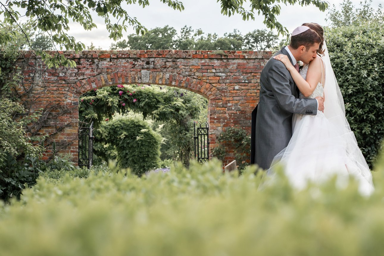 The walled garden at Stapleford Park is an ideal location for bride and groom photos. In this colour photo, the groom is kissing the bride's shoulder.
