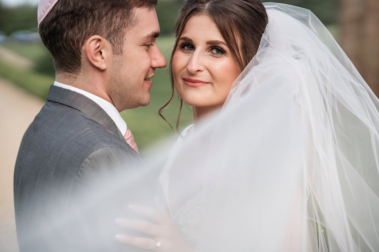 The bride looks over her veil blowing in the wind while her husband looks at her.