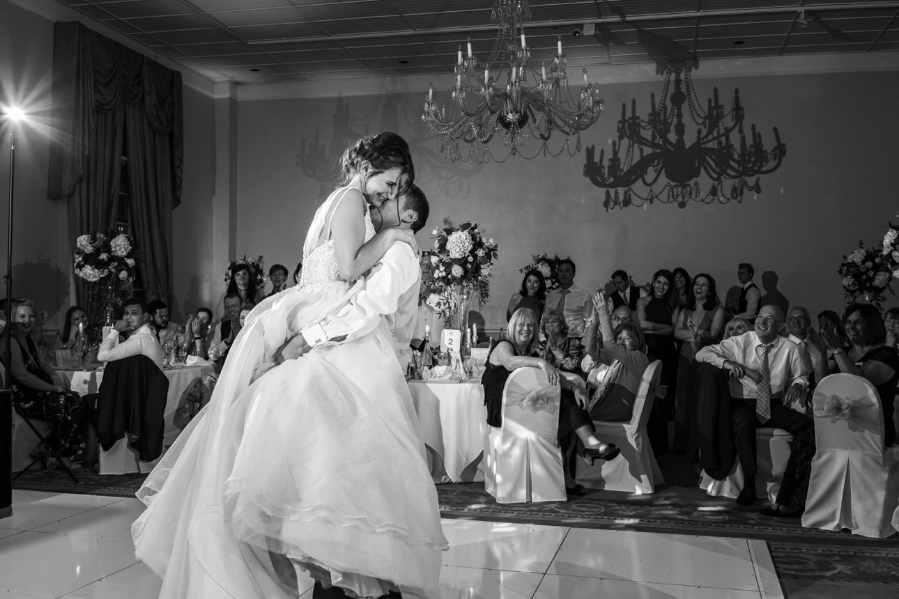 The groom swings his bride up into his arms during their first dance as newlyweds.