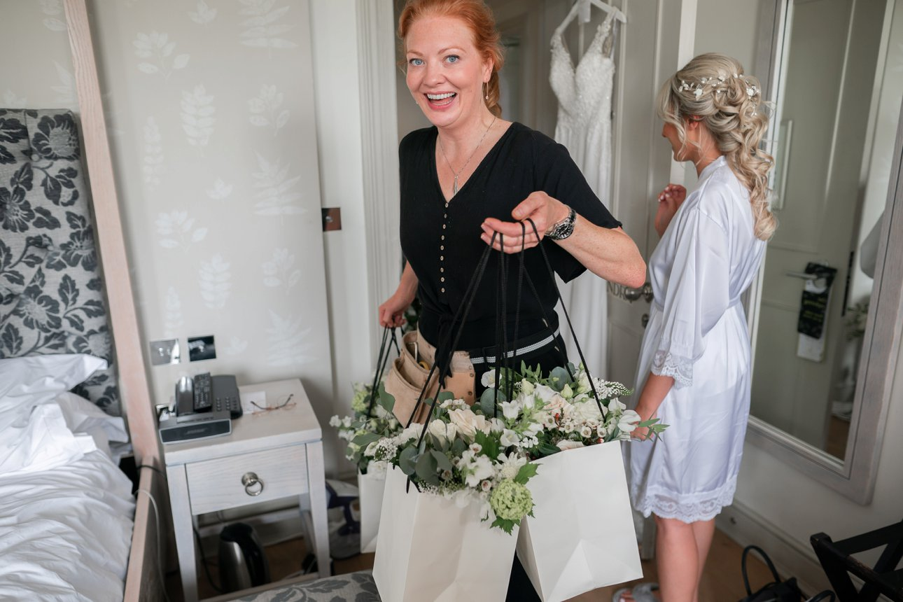 Florist Rebecca Marsala arrives with the bridemaids' bouquets and bridal bouquet for Laura's wedding at Stoke Place Slough.