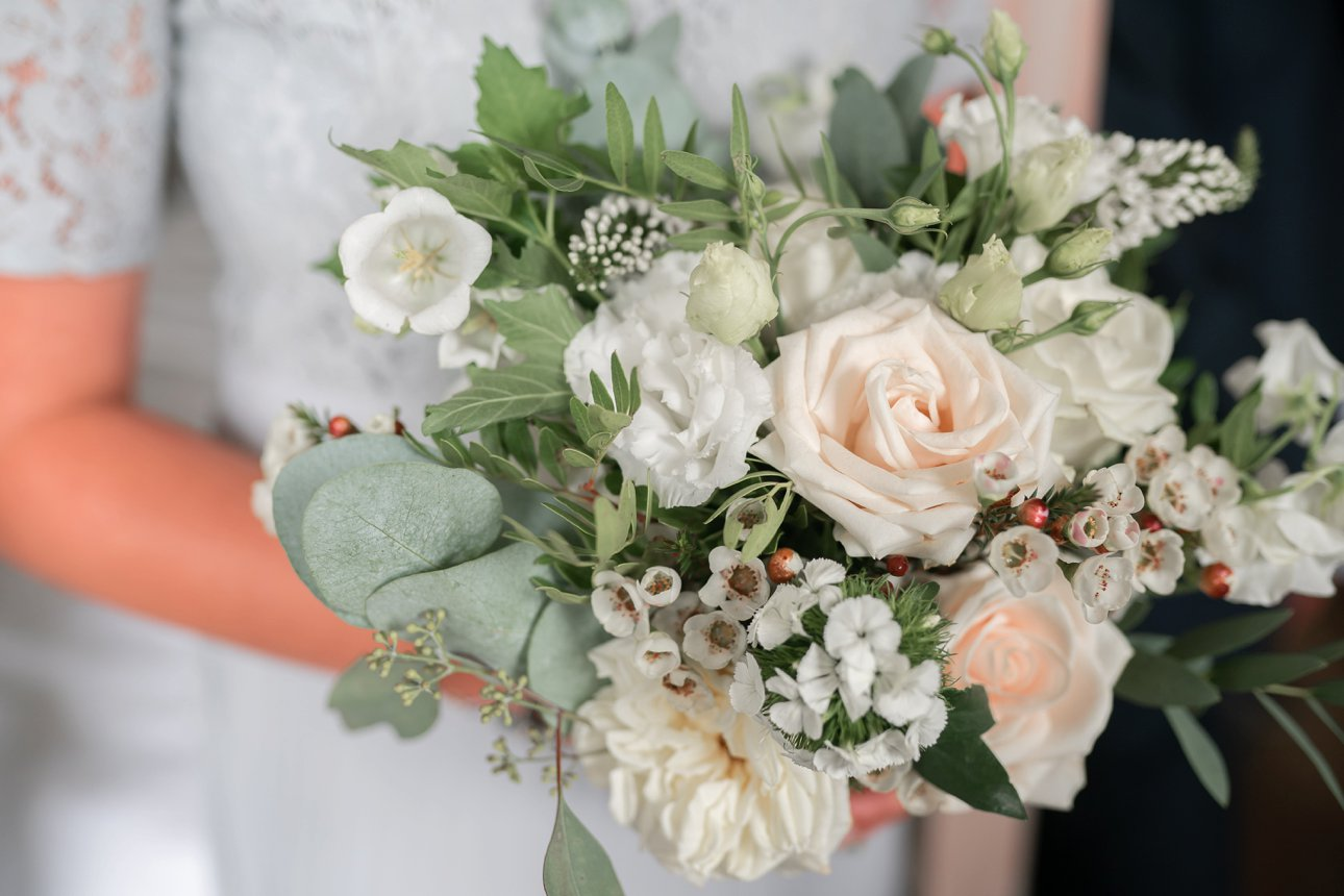 A bridesmaid holds a summer wedding bouquet by Buckinghamshire florist Rebecca Marsala.