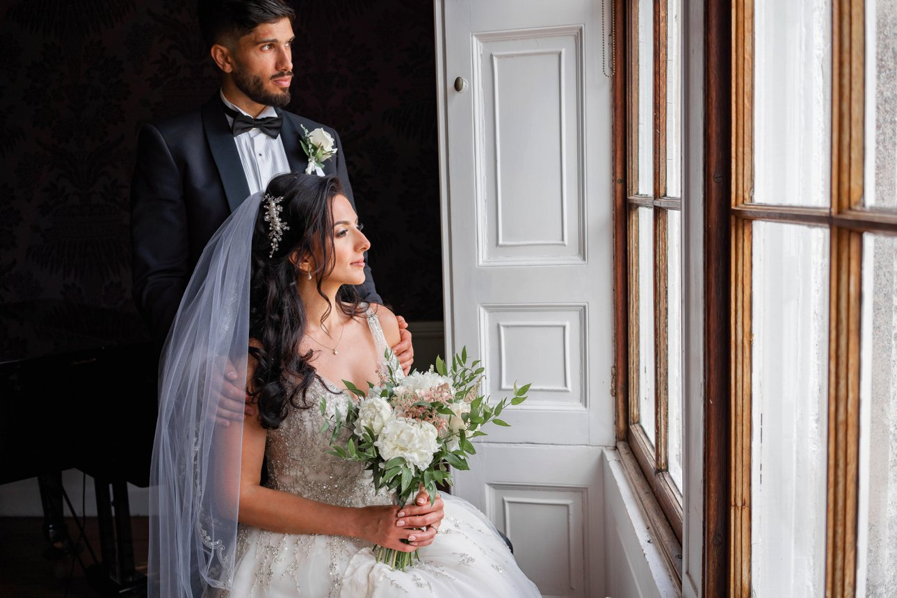 A couple looks out of the windows of Froyle House on their wedding day.