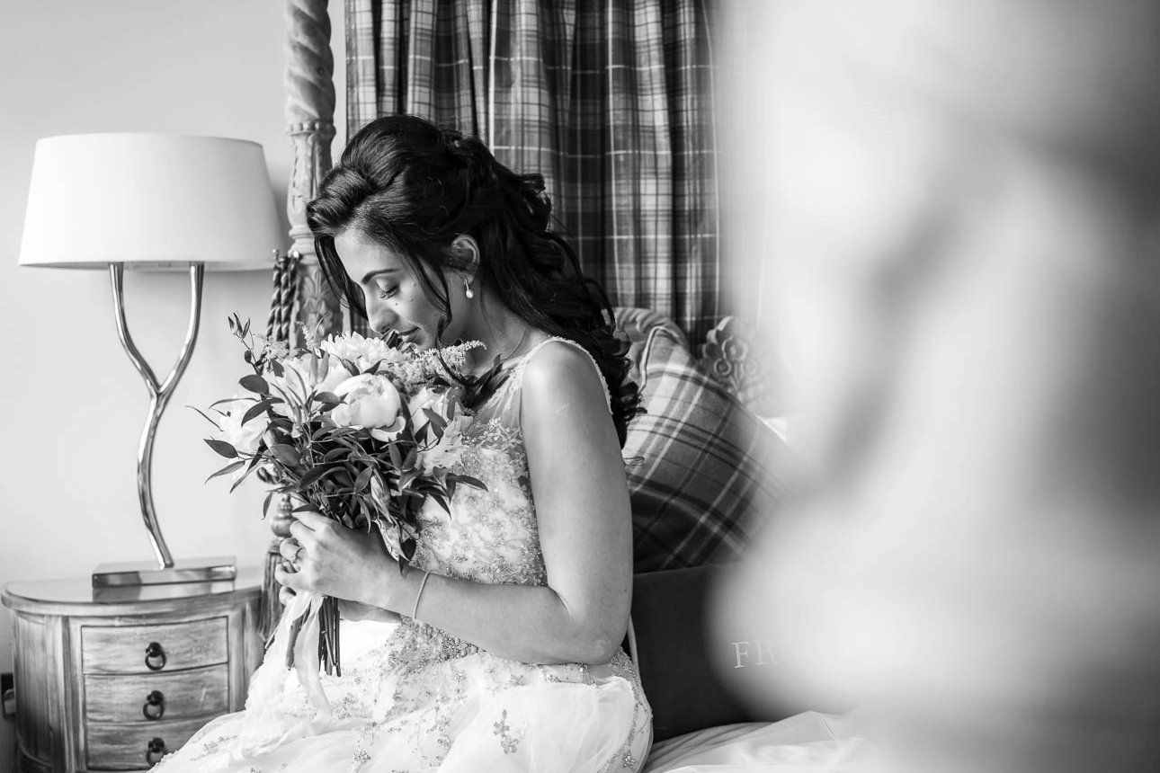 Black and white photo of a bride smelling her wedding bouquet before her wedding ceremony at Froyle Park in Hampshire.