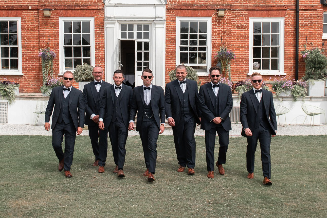 The groom, his best man and groomsmen dressed in suits and bow ties pose for photos outside Stoke Place Slough.