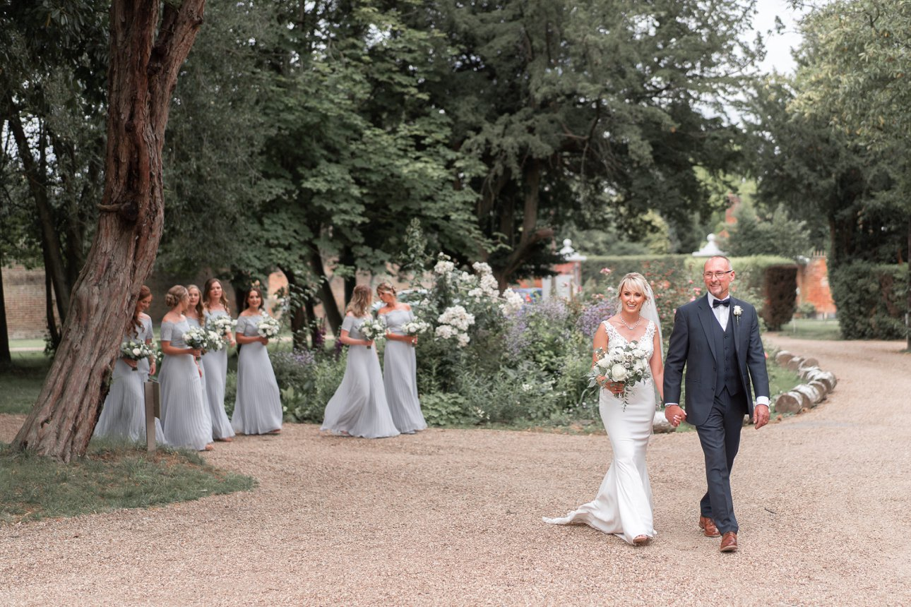 Colour photo of bride Laura and her father leading the bridesmaids in blue to Stoke Place Slough for the wedding ceremony.