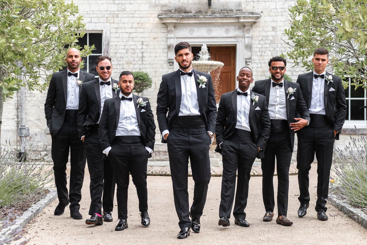 A groom and groomsmen in a group photo. All are dressed in black tie: tuxedos and black bow ties with cummerbunds.