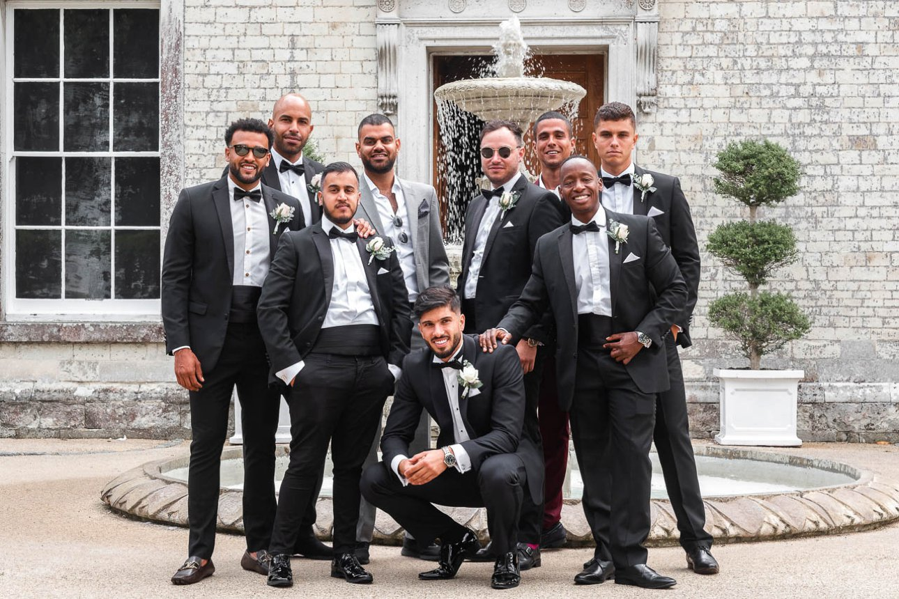 A groom, his best man and groomsmen group in front of the fountain at Froyle Park Country Estate for a formal wedding photo.
