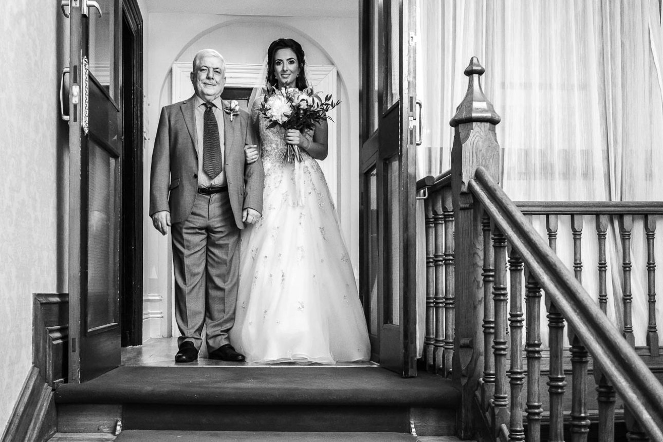 The bride and her father pause at the top of the Froyle Park staircase for a photo before her wedding.