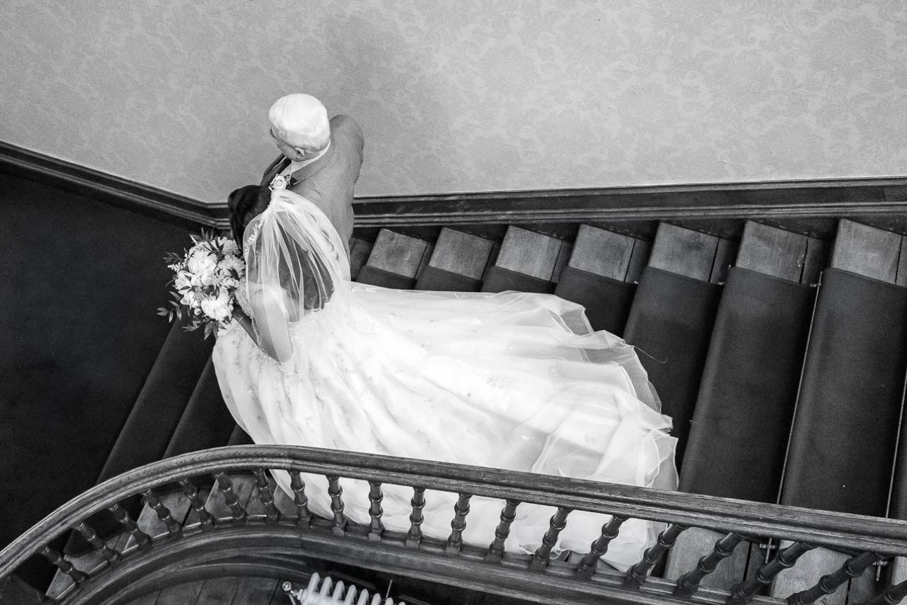 A photo of the bride and her father walking down the staircase of Froyle Park Country Estate before her marriage ceremony.
