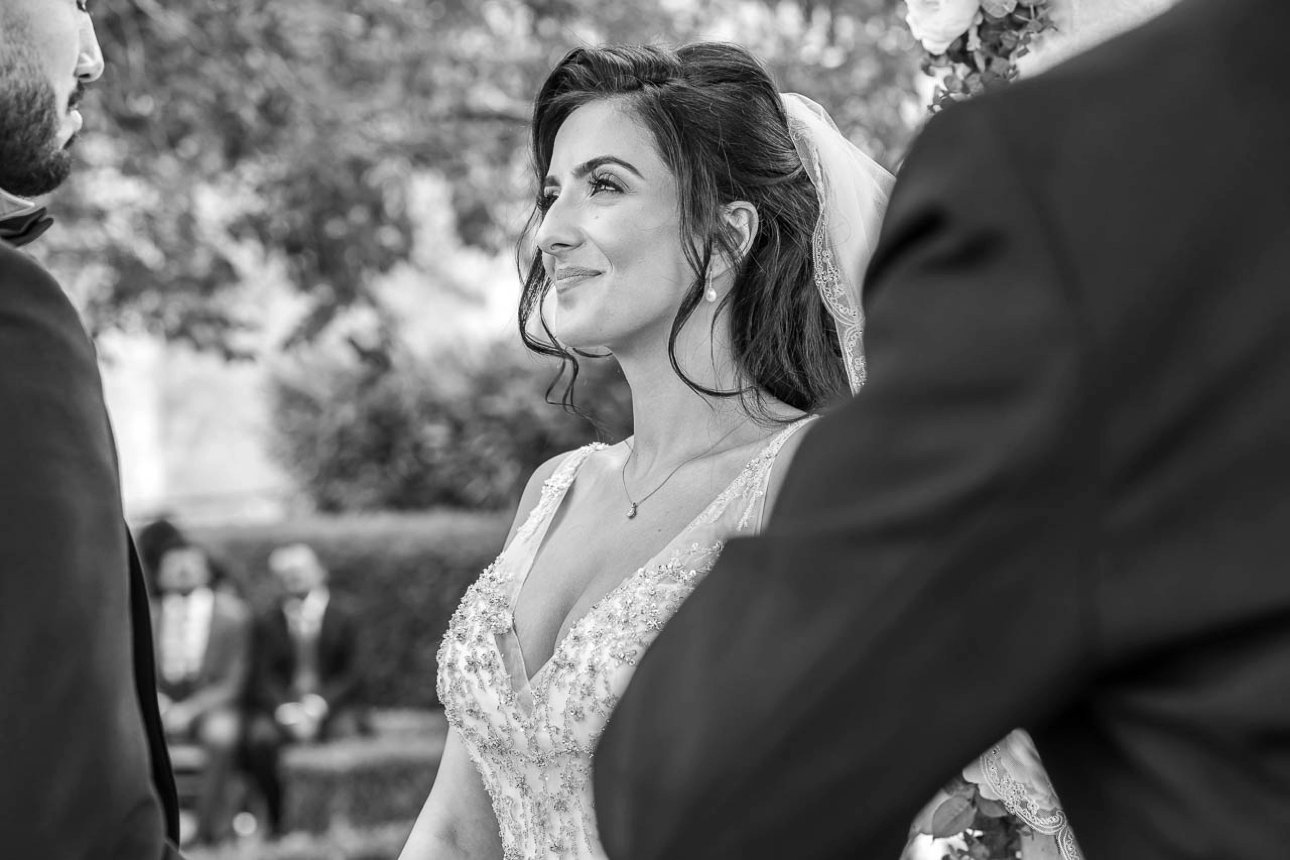 A black and white photo of a bride smiling at her groom during their summer outdoor wedding ceremony at Hampshire wedding venue Froyle Park Country Estate.