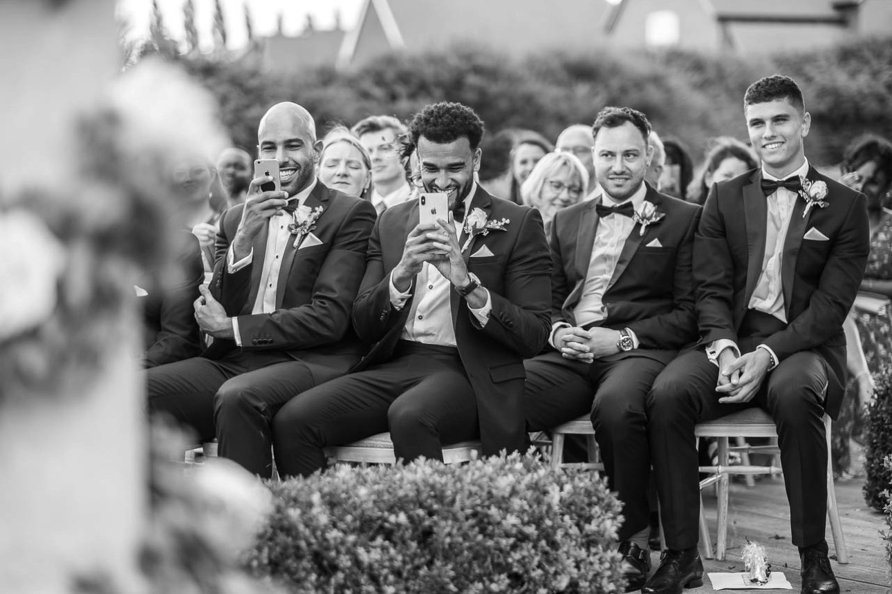 The tuxedo-wearing groomsmen watch the ceremony and film it with their phones while they're seated as guests at an outdoor wedding ceremony.