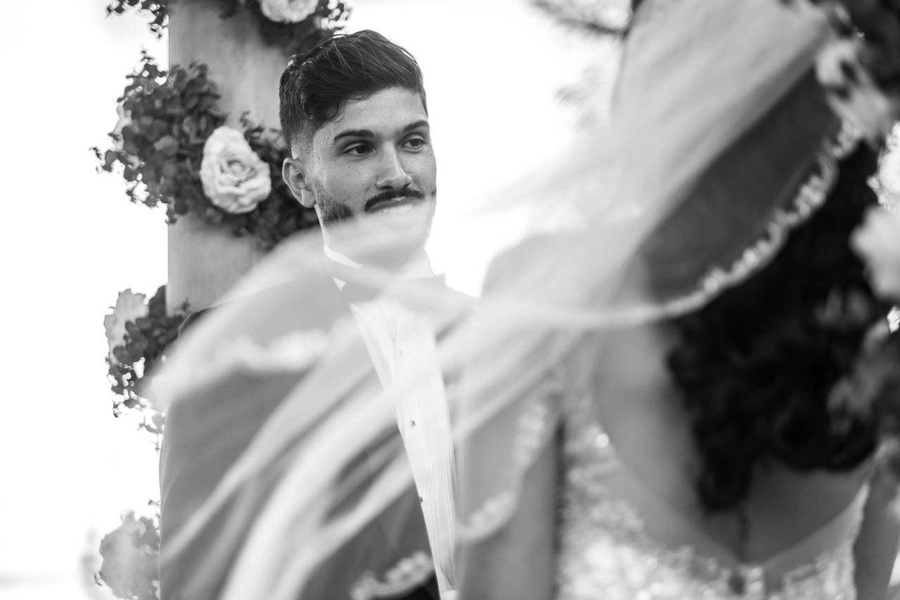 The groom smiles at his beautiful bride while her veil blows in the wind.