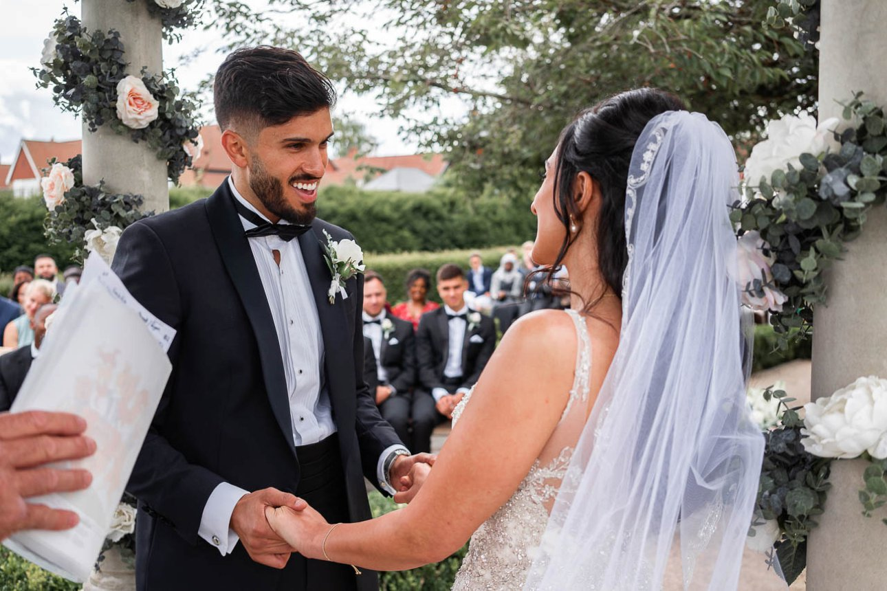 The groom smiles as he and his former fiance are announced as man and wife during their Hampshire outdoor wedding ceremony.