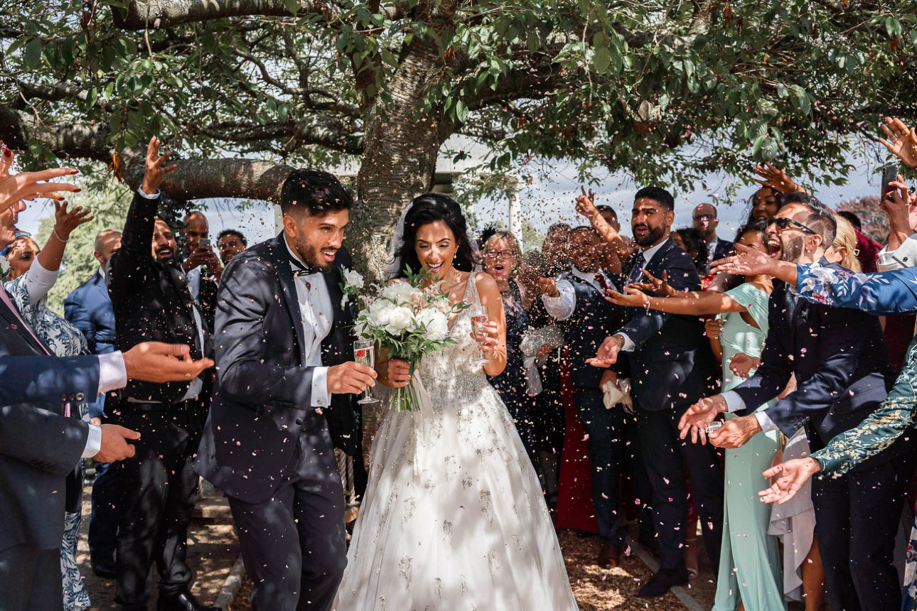 Rose petal confetti is thrown over the bride and groom after their wedding ceremony at Froyle Park Country Estate in Hampshire.