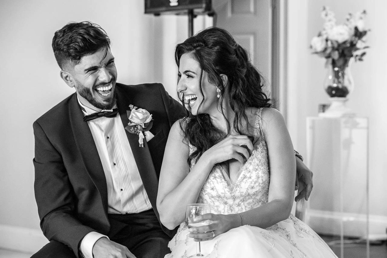 A black and white photo of the bride and groom sharing a laugh during the speeches at their Froyle Park wedding reception.
