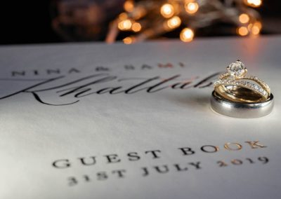 A-couple's-wedding-rings-sit-on-their-guest-book-ready-for-their-wedding-guests-to-sign.