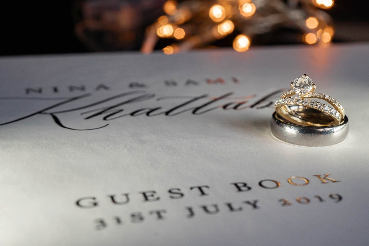 A couple's wedding rings sit on their guest book, ready for their wedding guests to sign.