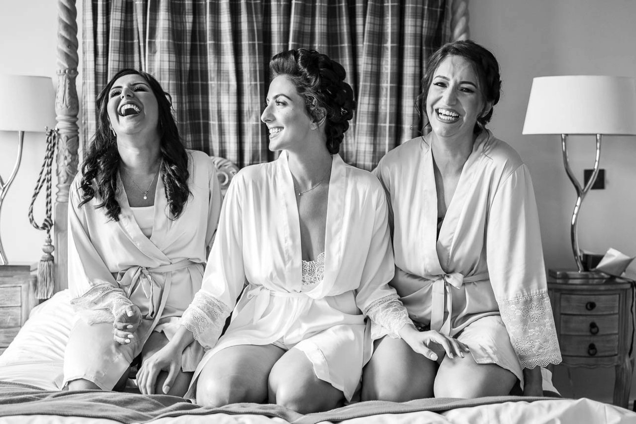 A bride and her bridesmaids sit in matching robes on her bed at Froyle Park Country Park.