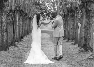 groom-kissing-bride-hand-walking-down-aisle-of-trees