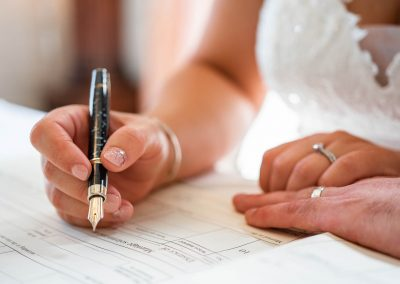 bride-and-groom's-hands-with-a-fountain-pen-at-their-signing-of-the-register.