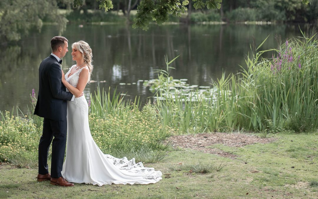 A bride and groom pose for a wedding portrait at Stoke Place Slough in Buckinghamshire after their summer wedding.