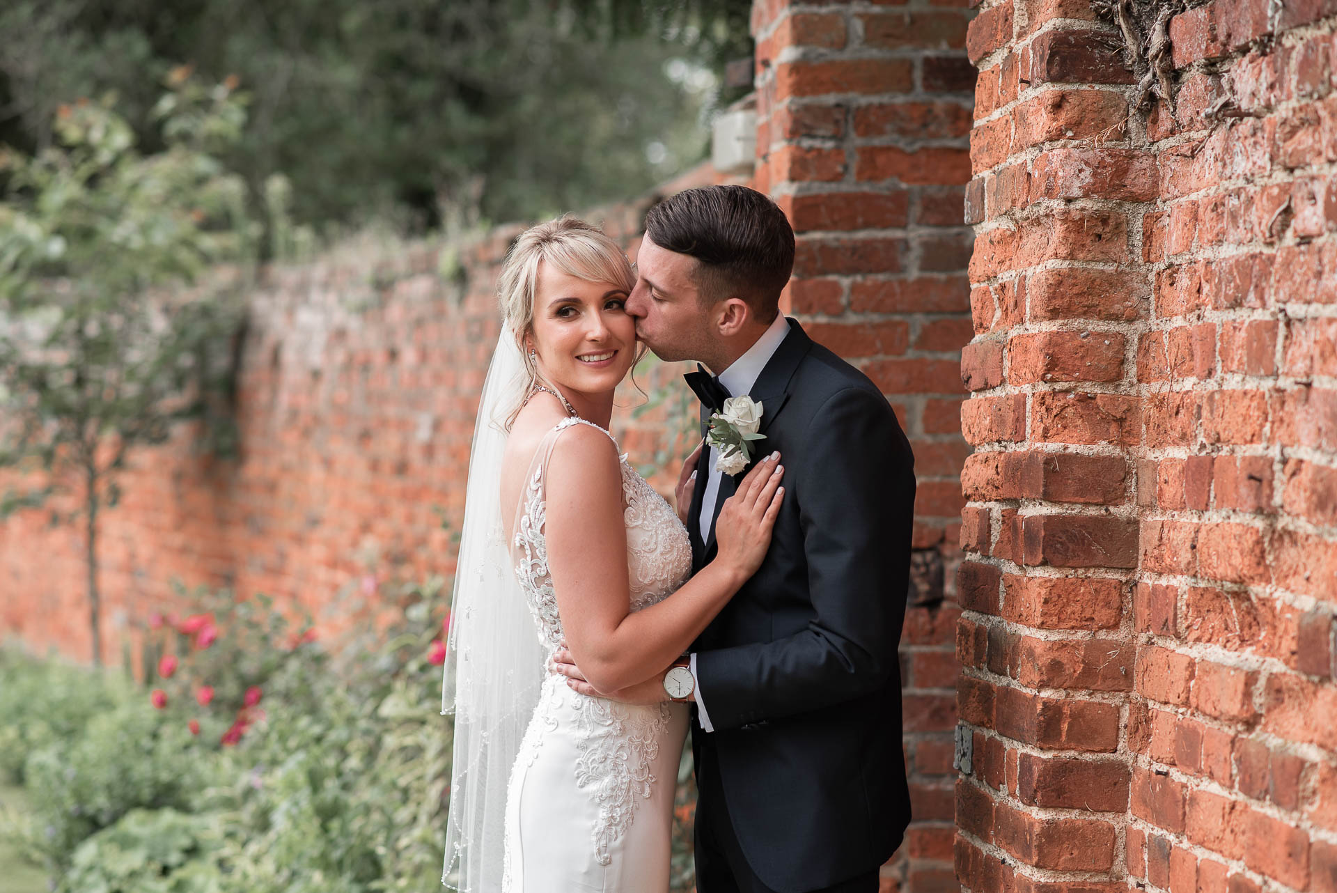 bride-and-groom-kissing-by-walled-garden