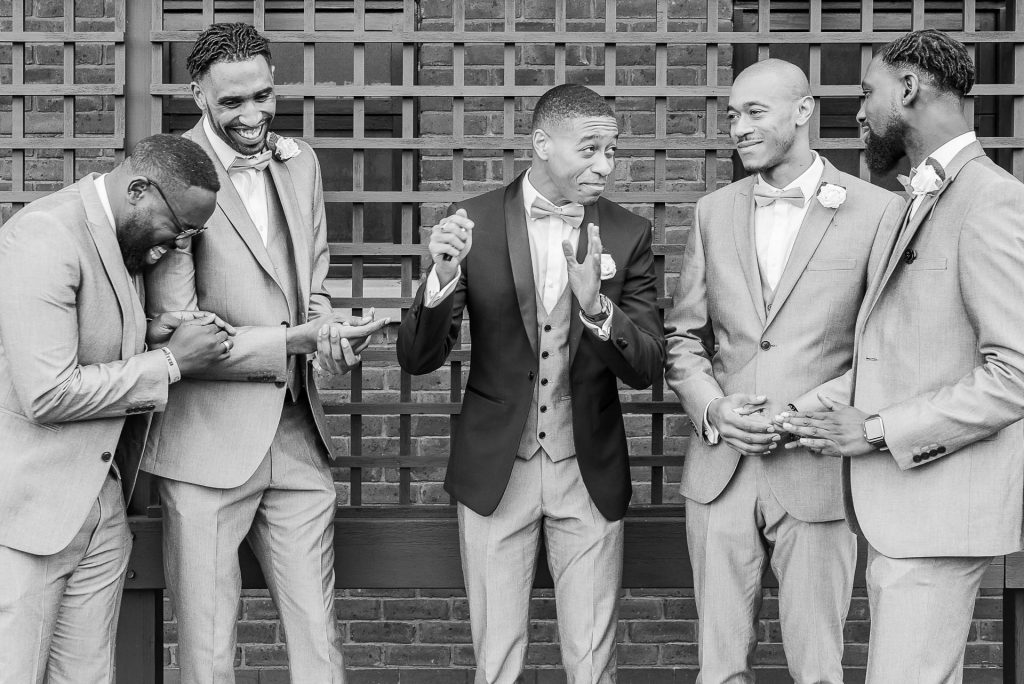 The groom and his men lark around during portraits.