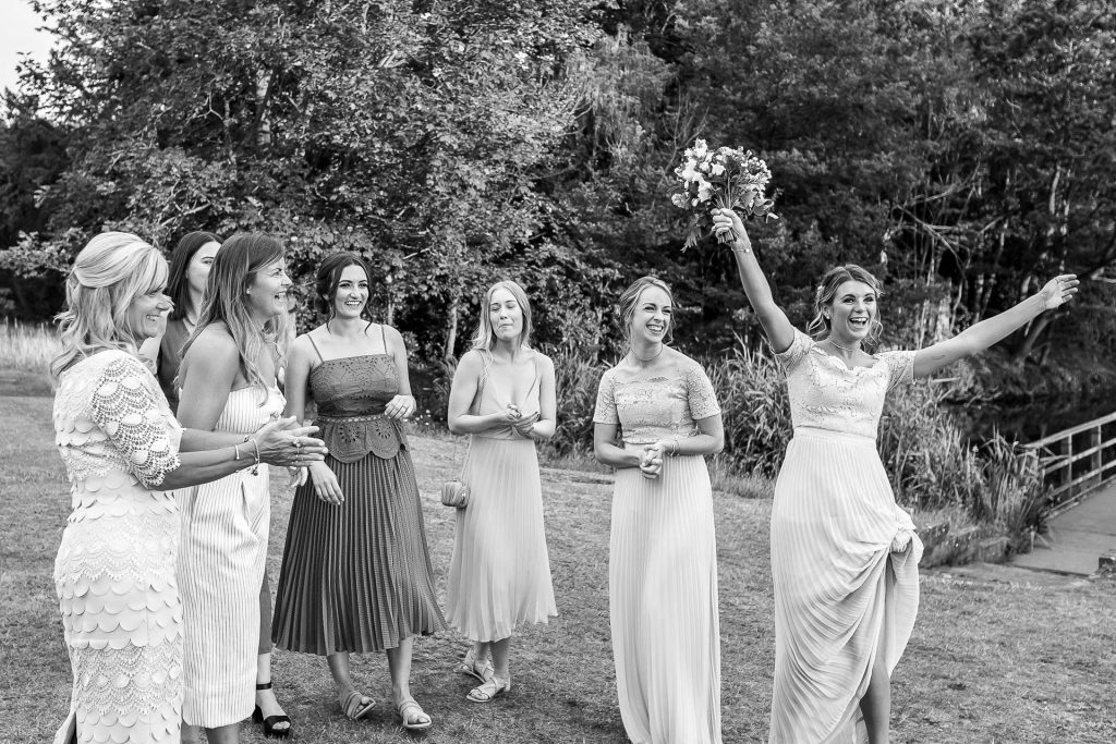 A wedding guest dances around with joy after having caught the bride's bouquet.