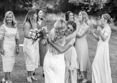 bride-tossing-her-bouquet-to-her-bridesmaids-girls-hugging