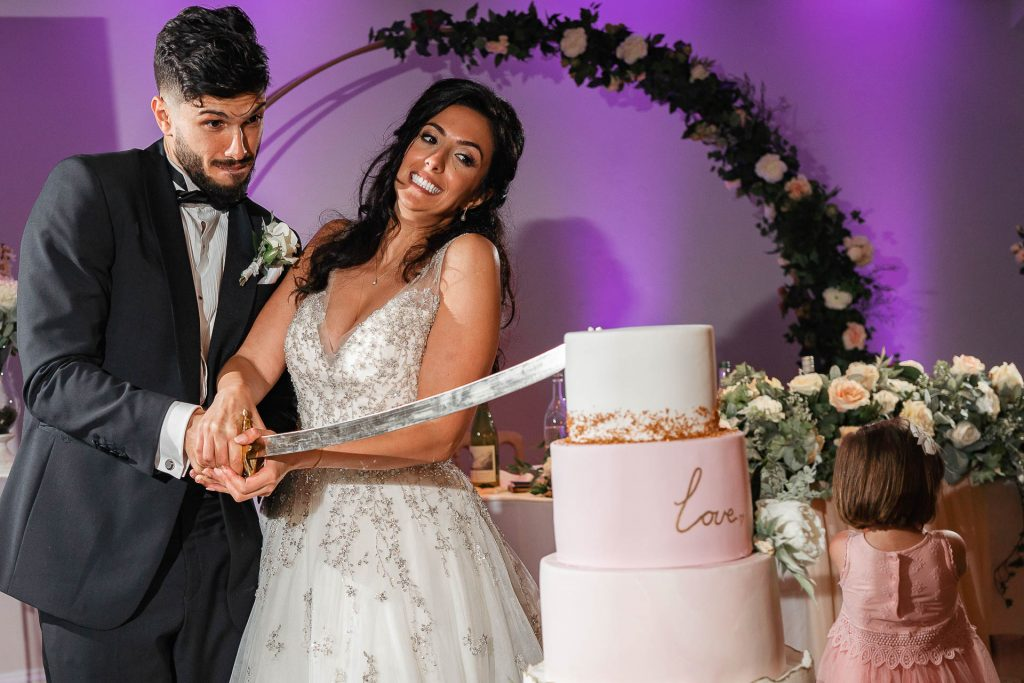 A bride and groom use a sword to cut their three-tier wedding cake.