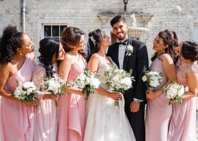 groom-smiling-with-bride-and-bridesmaids.