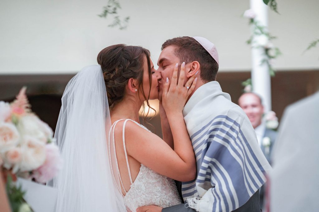 A Jewish bride and groom kiss after their wedding ceremony.