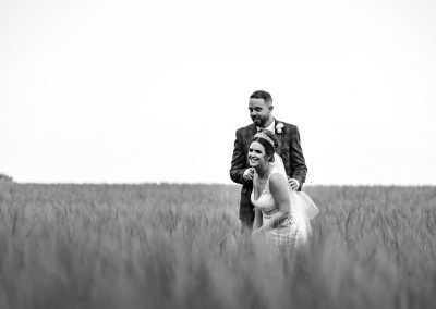 bride-and-groom-in-long-grass-field-laughing