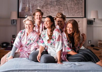Bride-on-the-bed-with-her-bridesmaids-morning-of-the-wedding-