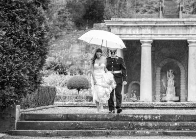 Black-and-white-portrait-of-bride-and-groom-taking-walk-in-the-rain