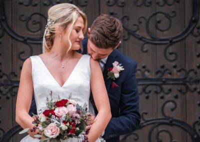 groom-kissing-shoulder-of-bride-outside-st-mary's-church