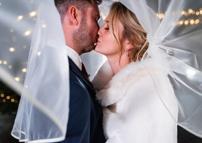 couple-kissing-under-brides-white-veil-with-fairy-lights